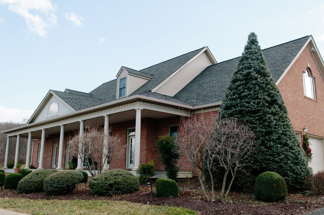 Brick Home With Shingle Roof & Gutters